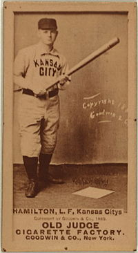 A sepia-toned image of a man in a white old-style baseball uniform and dark pillbox cap; he is holding a baseball bat in front of him in both hands