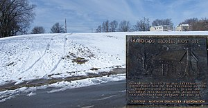 Temple Lot - Site of Boggs home on the Mormon Walking Tour with an inset blow up of the marker. The marker is on a cleared area of the sidewalk to the left of the blow up. The Independence Temple steeple is visible through the trees at the top of the hill.