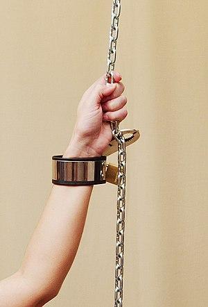 English: Photomodel bound with metal bondage c...