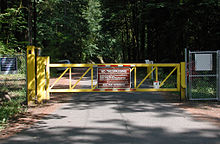 "A gate and fence block a forest road. Lettering on a warning sign on the gate says in part, ""No Trespassing: Bull Run Watershed"""