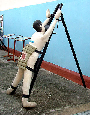"Caning in Malaysia - A mannequin tied to an A-shaped frame. Note the ""torso shield"" that covers the lower back and upper thighs while leaving the buttocks exposed."