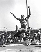 A man midway through a long jump leap.  There is a metal chainlink fence in the background, both in front of which and behind are a number of spectators