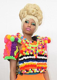 An Afro-American woman in a blonde wig and bright teal eyeshadow wears a shirt constructed of variously colored cotton balls
