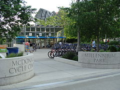 "Opposing stone entrances saying ""McDonald's Cycle Center"" and ""Millennium Park"" in front of parked bicycles and a two-story glass building"