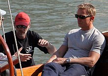 A man wearing a grey shirt, jeans and sunglasses sits on a boat at sea. Besides him, a man wearing a black shirt, red cap, and sunglasses talks to another, who is mostly off the picture.