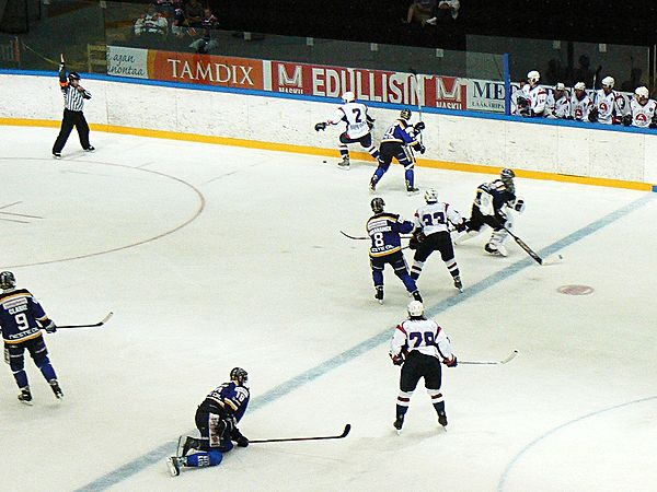 A delayed penalty call situation, in which the referee (top-left) indicates a coming penalty by raising his arm, and prepares to blow the whistle when a player from the team to be penalized (in white) touches the puck. Goaltender Jere Myllyniemi can be seen (right) rushing to the bench to send on an extra attacker. Delayed penalty.jpg