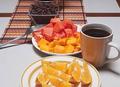 Desayuno de papaya, mango y naranjas con café.png