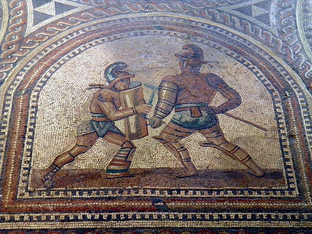 1024px-Detail_of_the_Gladiator_mosaic_floor%2C_a_Hoplomachus_fighting_a_Thraex%2C_R%C3%B6merhalle%2C_Bad_Kreuznach%2C_Germany_%288196100885%29.jpg