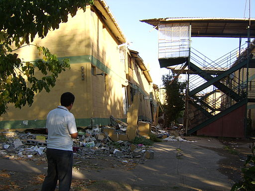 Diego Grez in front of destroyed apartments in Paniahue, Santa Cruz, Chile