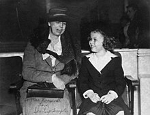 Photograph of Eleanor Roosevelt seated with Temple immediately to her left. The two are looking at each other apparently engaged in conversation.