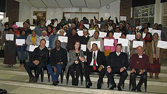 Free Market Foundation - Khaya Lam title deed giveaway ceremony in Grabouw, Western Cape on 25 July 2017. Seated in the front, left to right: Attie van Wyk (CEO of Two-a-Day), Isaac Sileku (Deputy Mayor of the Theewaterskloof Municipality), Christelle Vosloo (Mayor), Temba Nolutshungu (FMF director), Derek Corder (Trustee of the Elgin Foundation), and Perry Feldman (Khaya Lam project manager).
