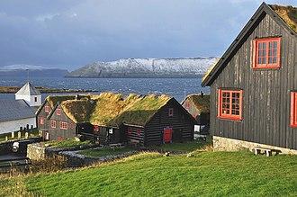 Kirkjubøur - Olavskirkjan at the left, Kirkjubøargarður  at the center. Background the islands Sandoy and Hestur.