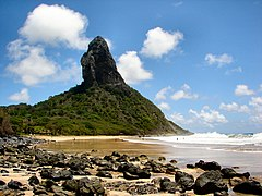 In the foreground, a wavy sea at the right and a yellow beach covered with black stones at the left. In the background, a mountain covered with green vegetation out of which towers a steep black rock.