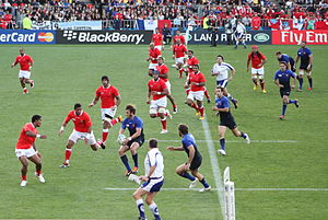 Comparison of association football and rugby union - A rugby union match from the 2011 Rugby World Cup showing the sport's distinguishing feature, the ball carrier leads his team up-field passing backwards in the event of a tackle