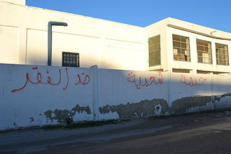 """Popular Front (Tunisia) - Graffiti tag on wall reading """"Popular Front against Poverty."""""""