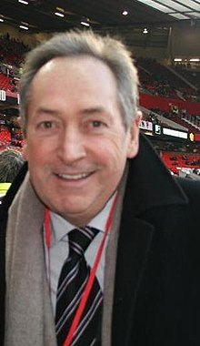 The upper body of a grey haired man. He is wearing a black coat, white shirt, black tie with blue stripes, grey scarf and a red ribbon is visible around his neck.