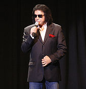A man wearing a black pin-striped sports coat with a red Handkerchief, a white dress shirt, blue jeans, and sunglasses, and holding a microphone