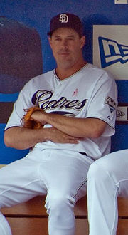 A man sits on a bench wearing a navy blue cap and a white baseball uniform in front of a blue wall