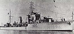 Three-quarter front view of destroyer with twin funnels and two forward gun turrets, at sea