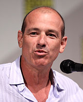 A balding man with a buttoned shirt in front of a microphone, and he is talking.