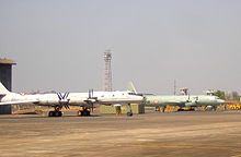 Two four-engine prop-driven aircraft on ramp facing right of screen. The large aircraft in the midground, which is slightly off-centered, has swept-back wings and is painted in a pale grey paints scheme. The other in the background is a straight-wing aircraft painted in pale green