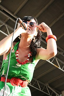 A dark-haired female in a green dress, heart-shaped sunglasses, and red costume jewelry sings into a microphone on stage. One hand is placed to her forehead.