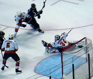 Miikka Kiprusoff -  alt = View from behind the left shoulder of a goaltender as he reaches out with his left hand and catches a puck shot into his glove as several players look on.