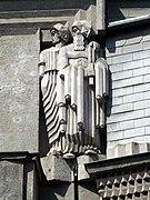 Une statue représentant deux personnages en pied, l'un masculin portant la barbe et l'autre vraisemblablement féminin, tous deux le regard vers la gauche, d'apparence anguleuse et très géométrique.