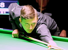Photograph of Kyren Wilson leaning across the table, holding a cue.