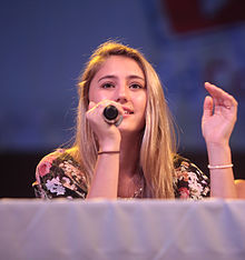 A teenage blonde girl with black floral patterned top, seated behind a table draped in a white cloth looking forward at an unseen audience; a microphone in her right hand is held to her mouth as she gestures with her left hand.