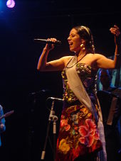 A woman in a flower dress singing to a microphone with her eyes closed.