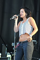 A woman with dark hair, wearing jeans and a cropped white top with black stripes, singing into a microphone
