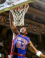 "A man, wearing a blue jersey with a word ""PISTONS"" and the number ""23"" written in the front, is trying to dunk a basketball."