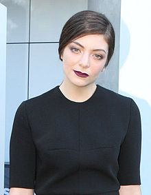 Lorde is wearing a black dress as she faces the camera.