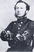 photograph of a man sitting upright, wearing a grey dress uniform