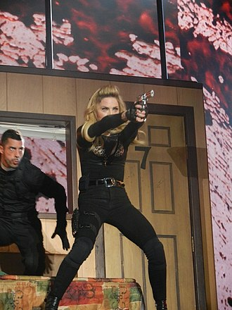 """MDNA (album) - Madonna performing album track """"Gang Bang"""" during The MDNA Tour's first segment; the tour caused controversy due to the use of firearms."""
