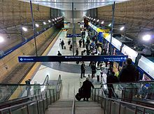 An underground center-platform railway station with sandy colored walls and people getting on and off a train on the right side of the image. Taken from the top of an escalator looking down.