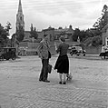 Man talking to woman in cobbled square, church visible in background, Co. Dublin (34195798906).jpg