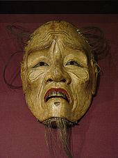 Masque en bois non peint, sauf les lèvres rouges, d'un vieillard émacié et ridé avec une barbiche et de rares cheveux.