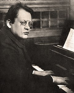 black-and-white photograph of a pianist posing at his instrument, with his hands on the keyboard at the bottom right, and his face halfway towards the camera