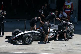 McLaren - Mechanics push Kimi Räikkönen's MP4-19 into the garage during qualifying for the US Grand Prix at Indianapolis in 2004.
