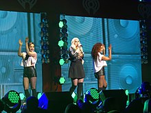 A young long-haired blonde woman singing into a microphone onstage. She sports a black skirt and black Bad Gal jacket, on her left and right are two brunette women dancing, each are wearing a sleeveless white top and leather shorts. A portraits of several bass speakers squared in pattern with background colors of neon green as the women's backdrop, as well as the iHeart Radio logo.
