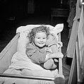 Meisje liggend in haar ledikantje met een speelgoedbeer, Bestanddeelnr 252-9355.jpg