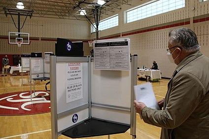Michael Georg Link examines a voting booth in Washington, DC, 3 Nov. 2020 (50564571952).jpg