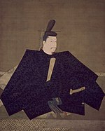 Portrait in three-quarter view of a person seated on the floor in courtly attire carrying a stick like object.