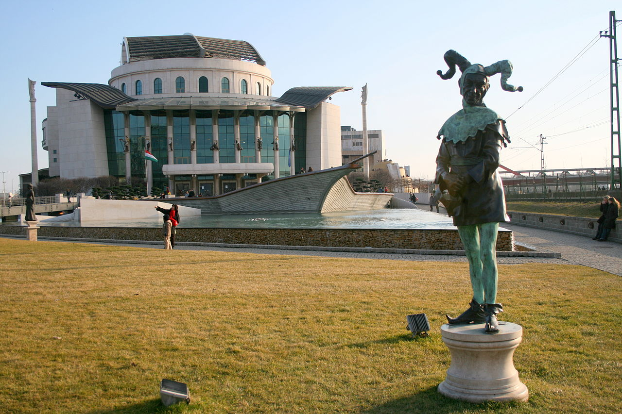 Statue in the foreground of a picture of the National Theater