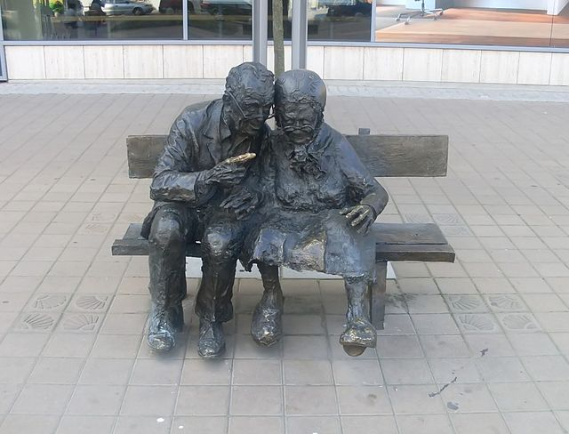 Bronze sculpture of an elderly Kashubian married couple located in Kaszubski square, Gdynia, Poland, which commemorates their monogamous fidelity, through the time of their separation, while he temporarily worked in the United States. Old marriage at Plac Kaszubski.jpg
