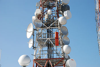 A Variety Of Parabolic Antennas On Communications Tower In Australia For Point To Microwave Communication Links Some Have White Plastic Radomes