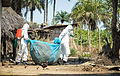 Pictured is a member of the Port Loko District Ebola Response Centre staff bring out contaminated items from a property under the supervision of the team coordinator. MOD 45158997.jpg
