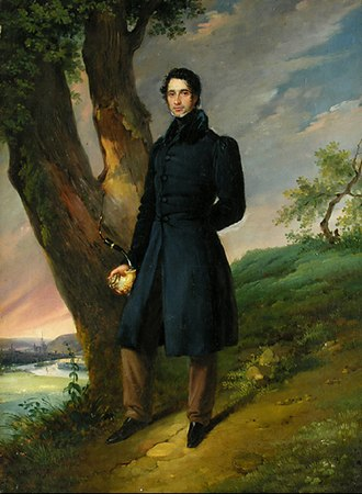 1820s in Western fashion - This man wears a dark coat with a high shawl collar. His sleeves have puffs at the shoulder and taper to the wrist. He wears light brown trousers, 1828.